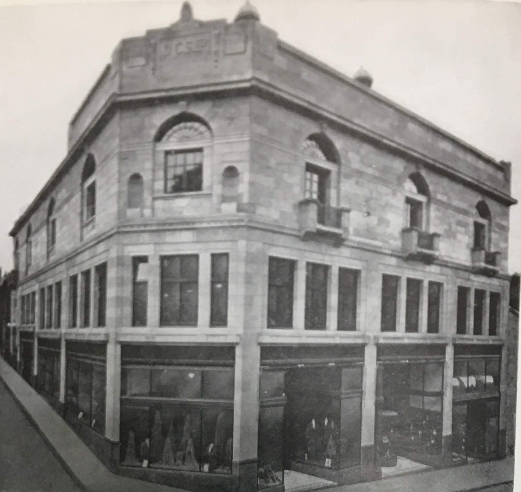 Photo showing Unitas Hall and shops, east corner of Queen Anne Street and Randolph Street.