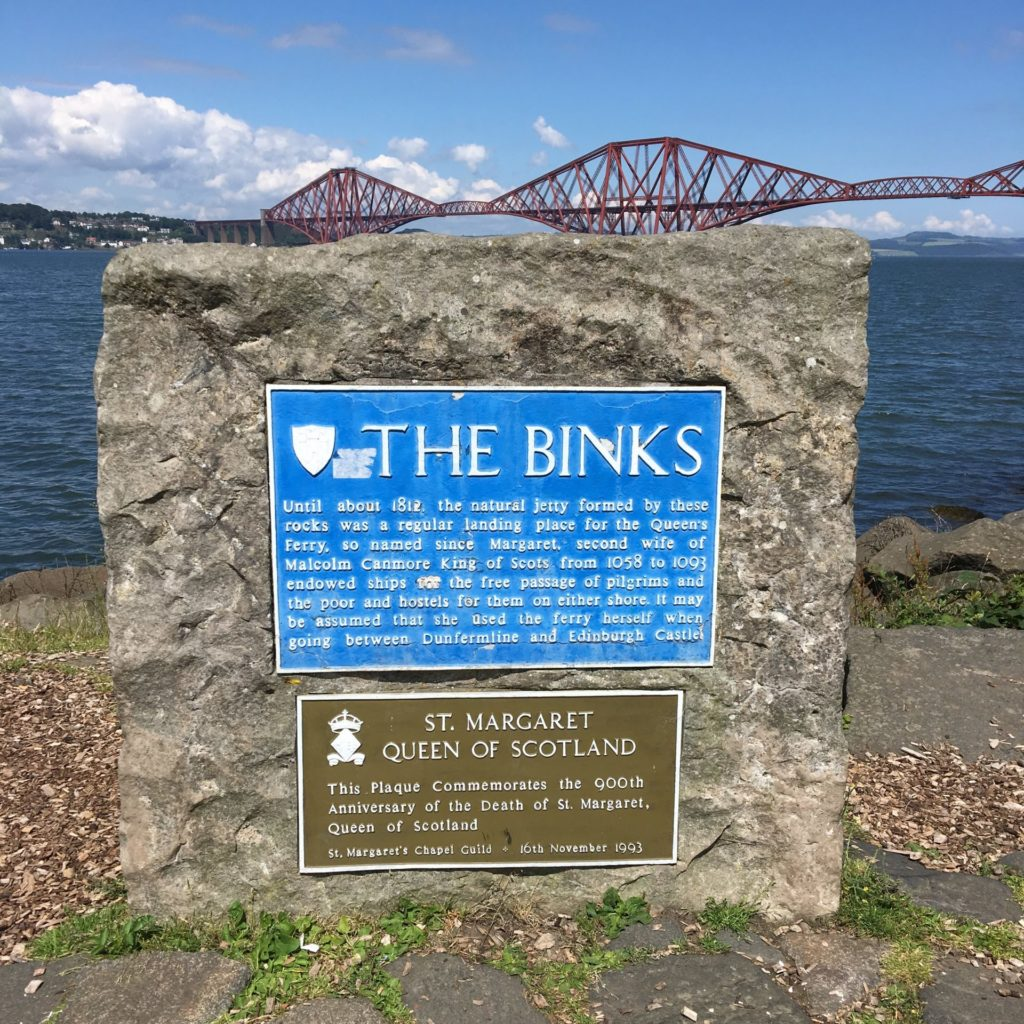 Stone with signs telling story of The Binks natural jetty and St Margaret Queen of Scotland. Behind is the sea and Forth Bridge.
