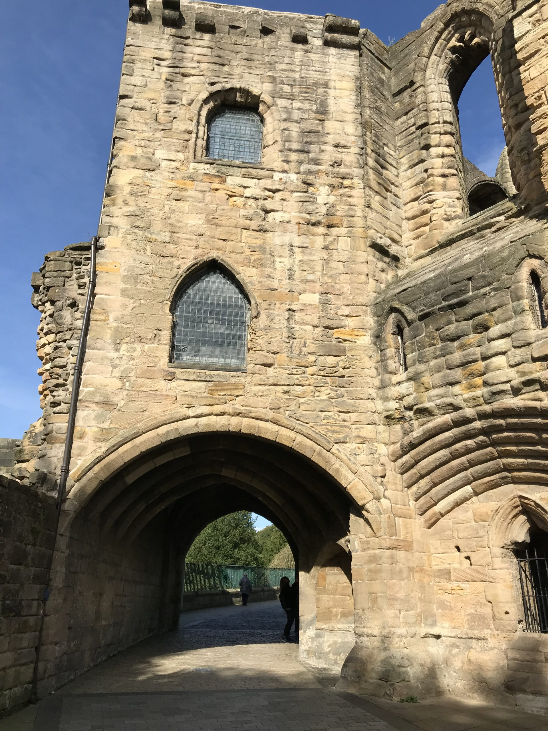 Stone building showing gateway arch called The Pends. Below tower from ruined Abbey buildings