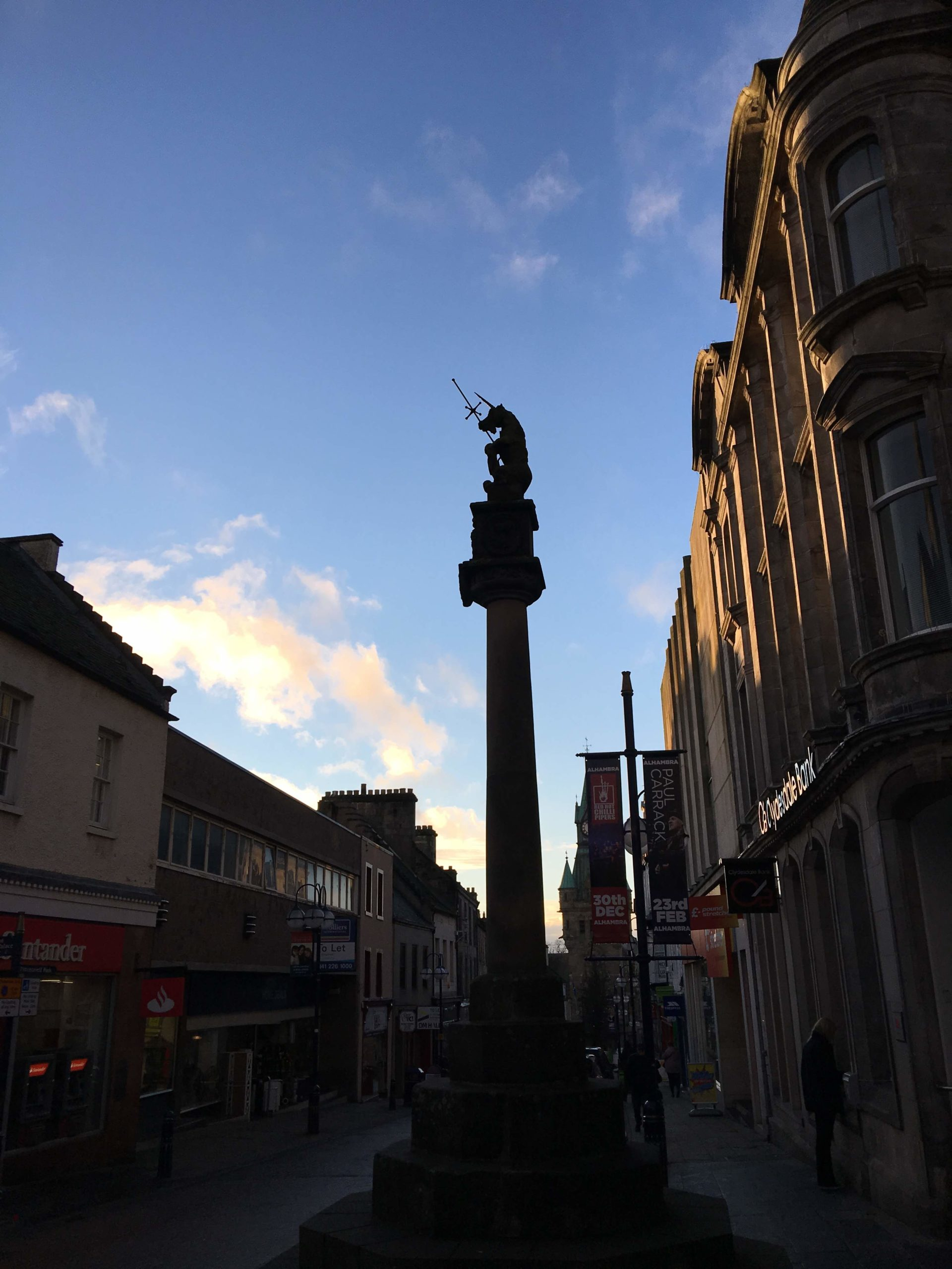 Dunfermline's Mercat cross topped with unicorn and sceptre in afternoon shade against a blue sky background.