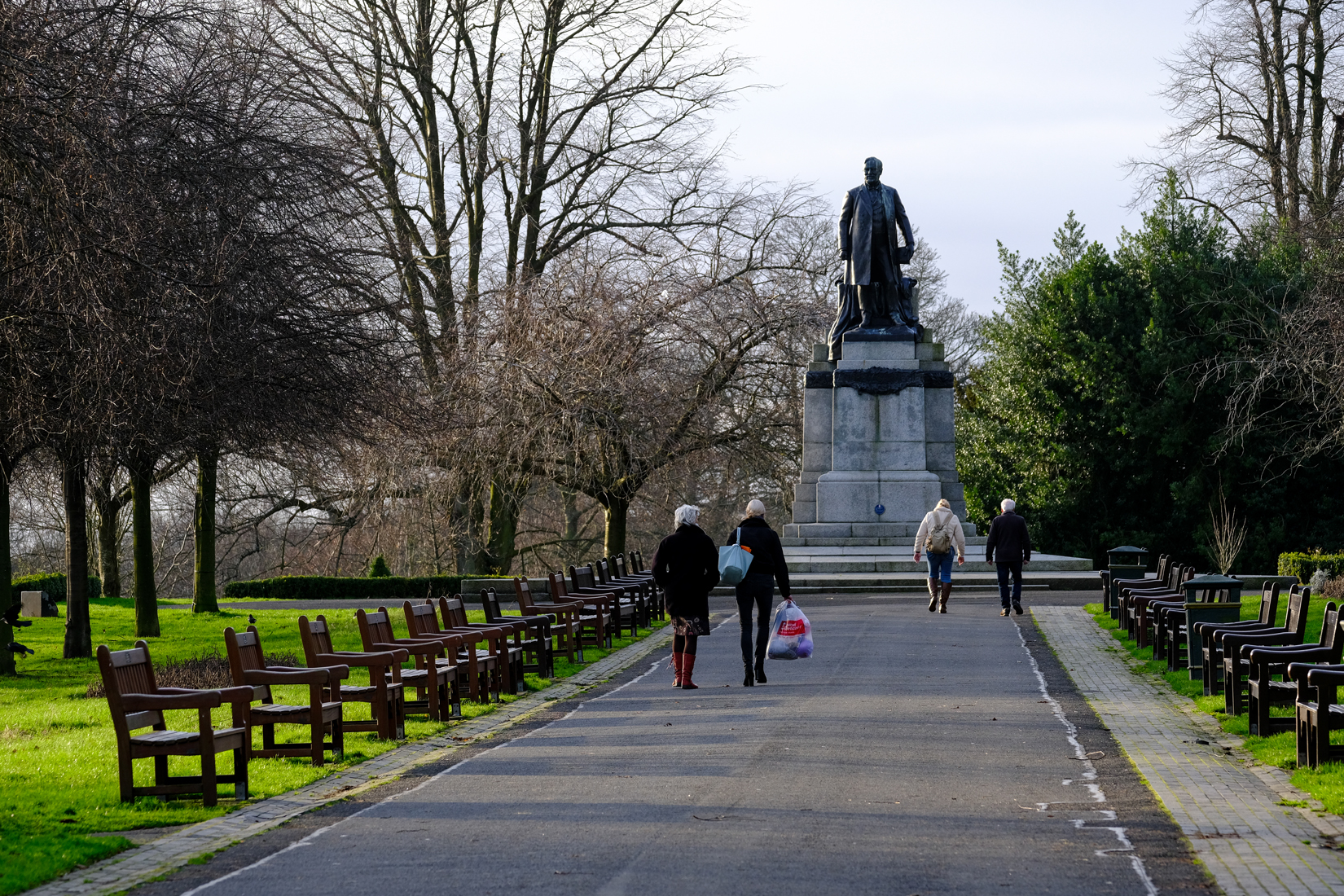 Pathway with multiple wooden benches on either side. Four people on the path and heading towards statue at end of path with large metal cast of male standing atop stone plinth.