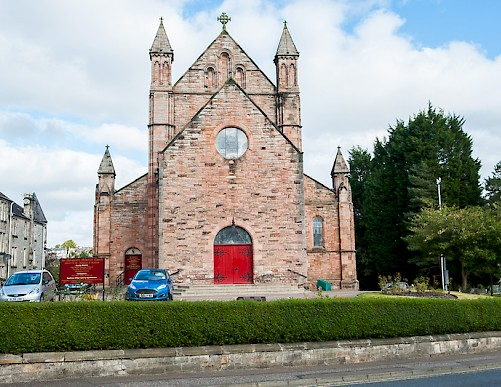 Pink or red stone church building with four towers. Two are on outside at 10m and then two more are forming a tower of 30m. Gable end with entrance door in the centre.