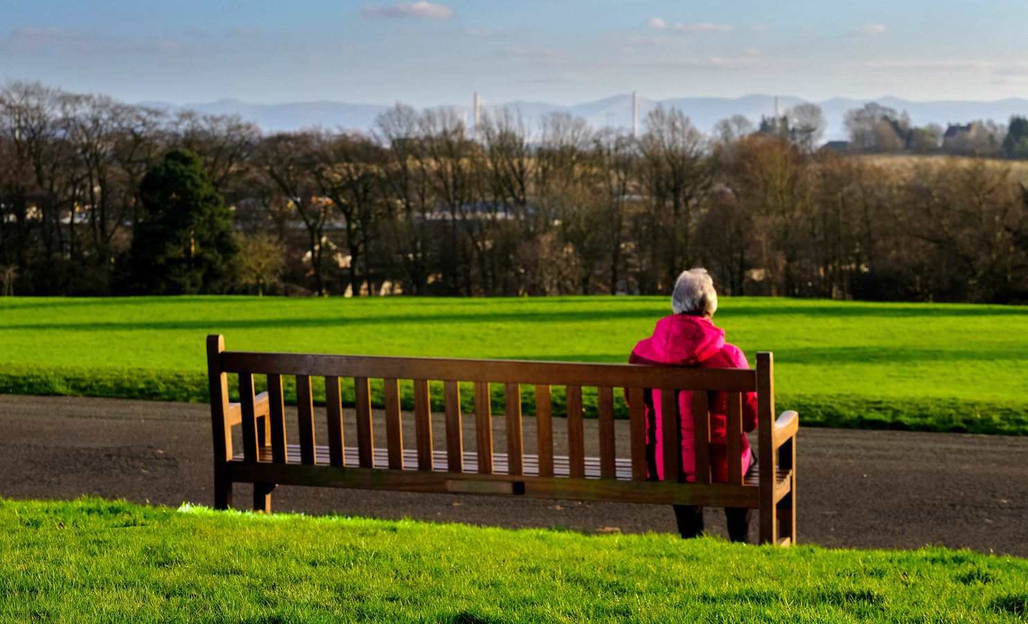 Back of a wooden bench in park with a person in red coat and grey hair sitting on the far right of 4m bench. In distance the park changes to trees, houses and Queensferry Crossing bridge and hills beyond.