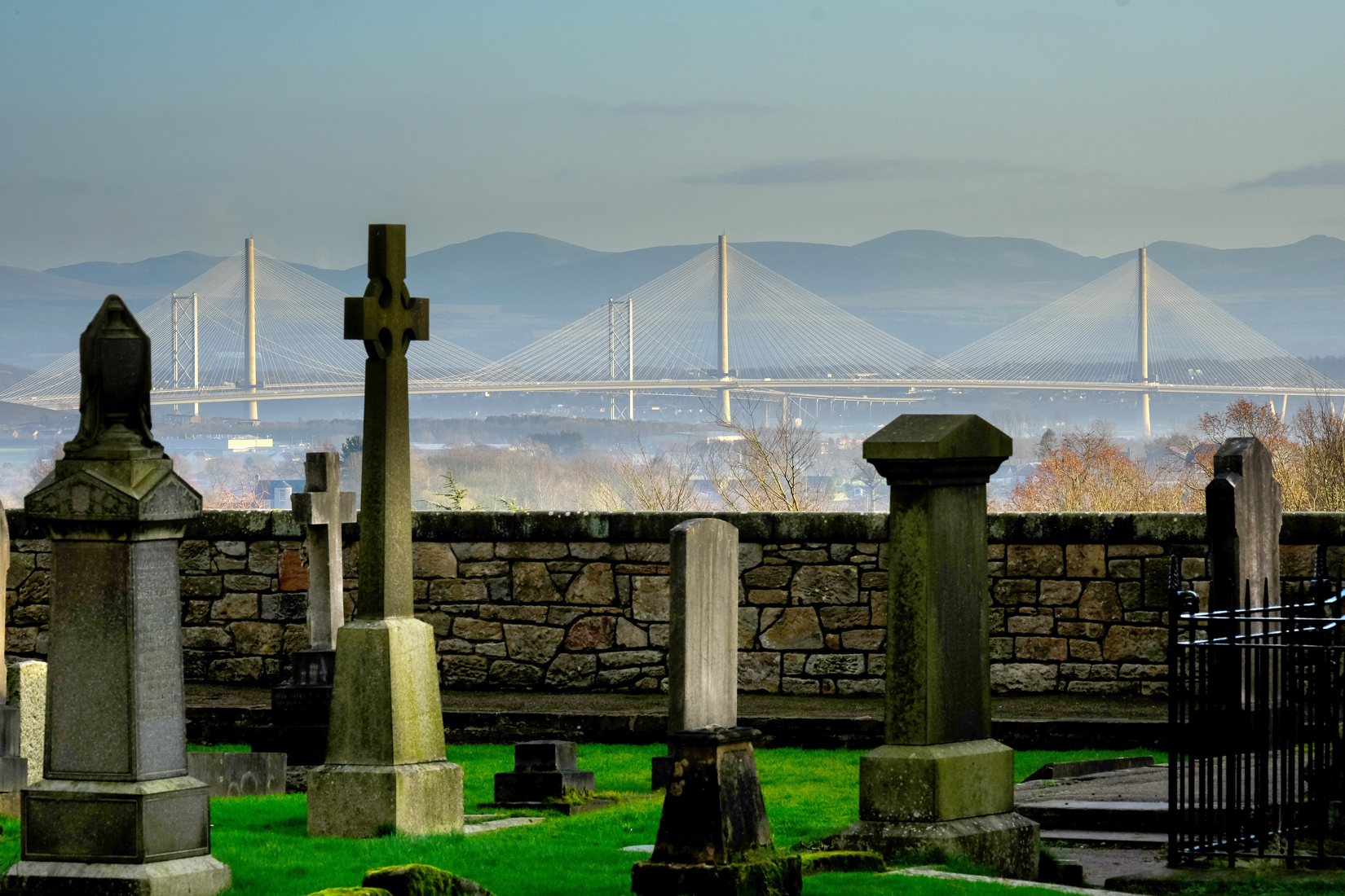 Grave stones in foreground and graveyard boundary wall. In the distance bridges across the Forth. Queensferry Crossing first and behind that Forth Road Bridge. Hills in the distant background