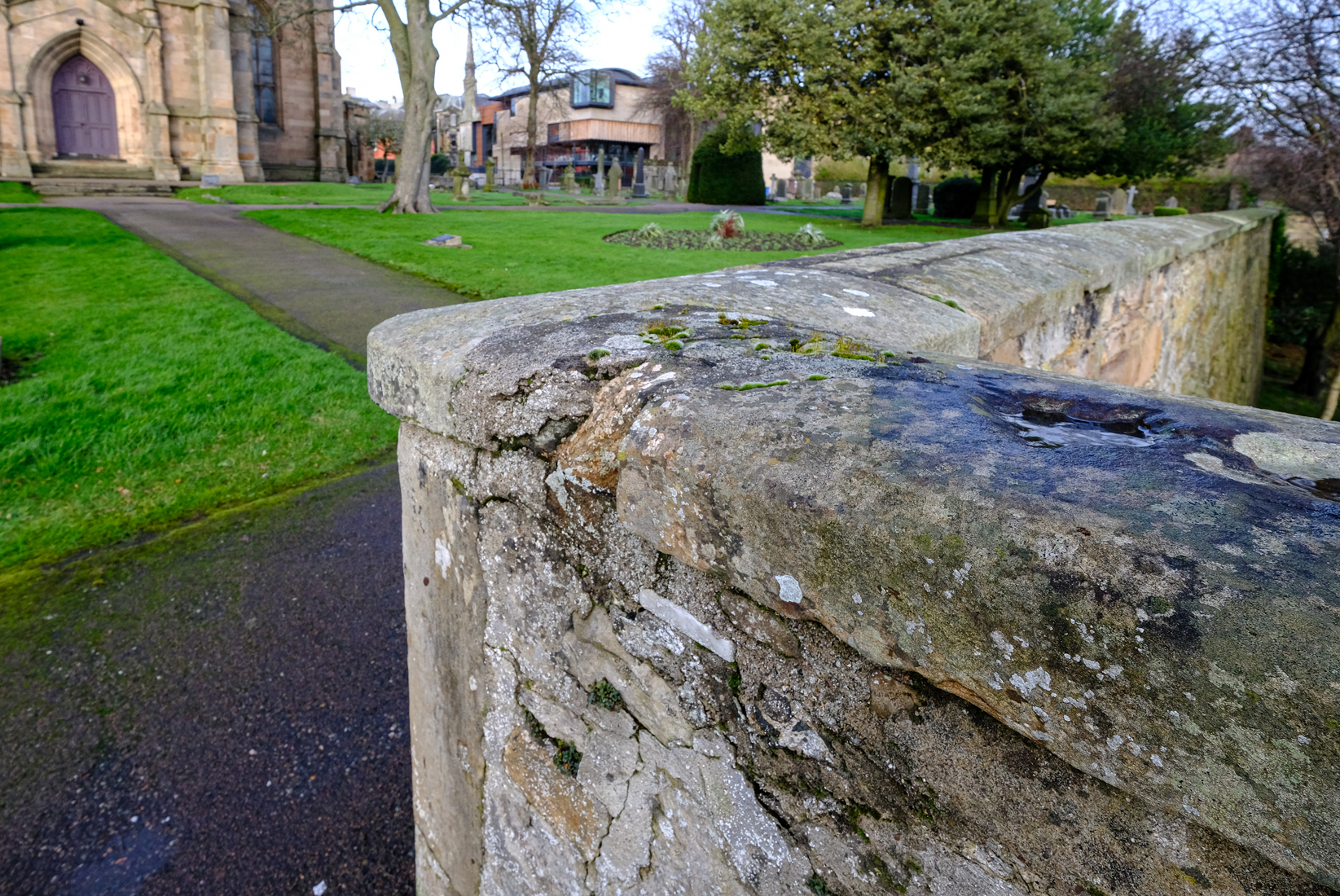 Corner of boundary wall for Abbey Graveyard. The wall is stone and 120cm high. About 20cm from top is a white rectangular stone 2cm tall and 10cm long