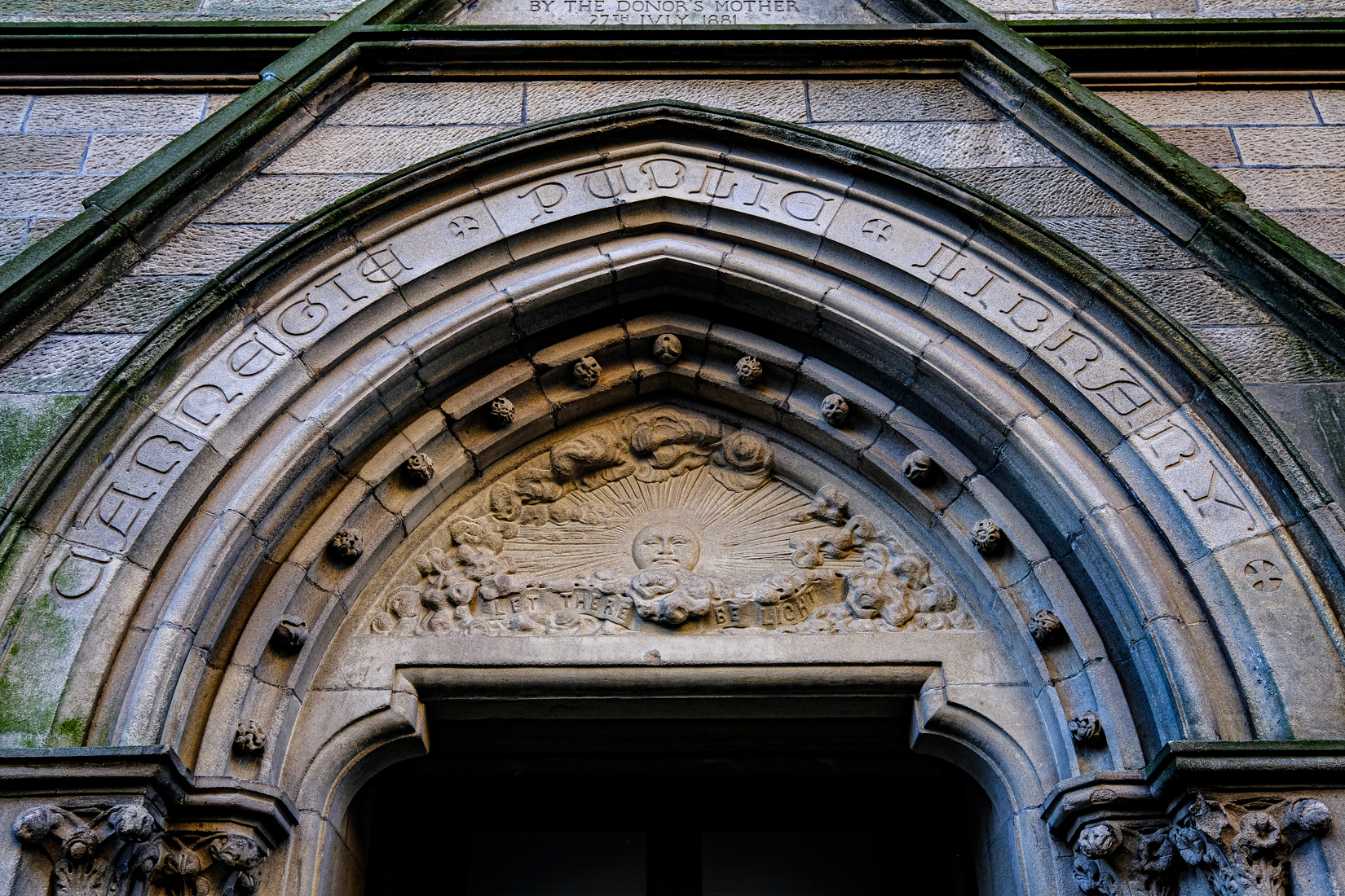 Carved stone arch reading Carnegie Public Library. Carved relief below of sun and rays with motto Let there be light.