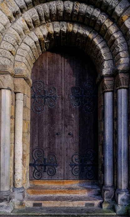 Two wooden doors, open in centre with five stone arches supported by 2m stone pillars.