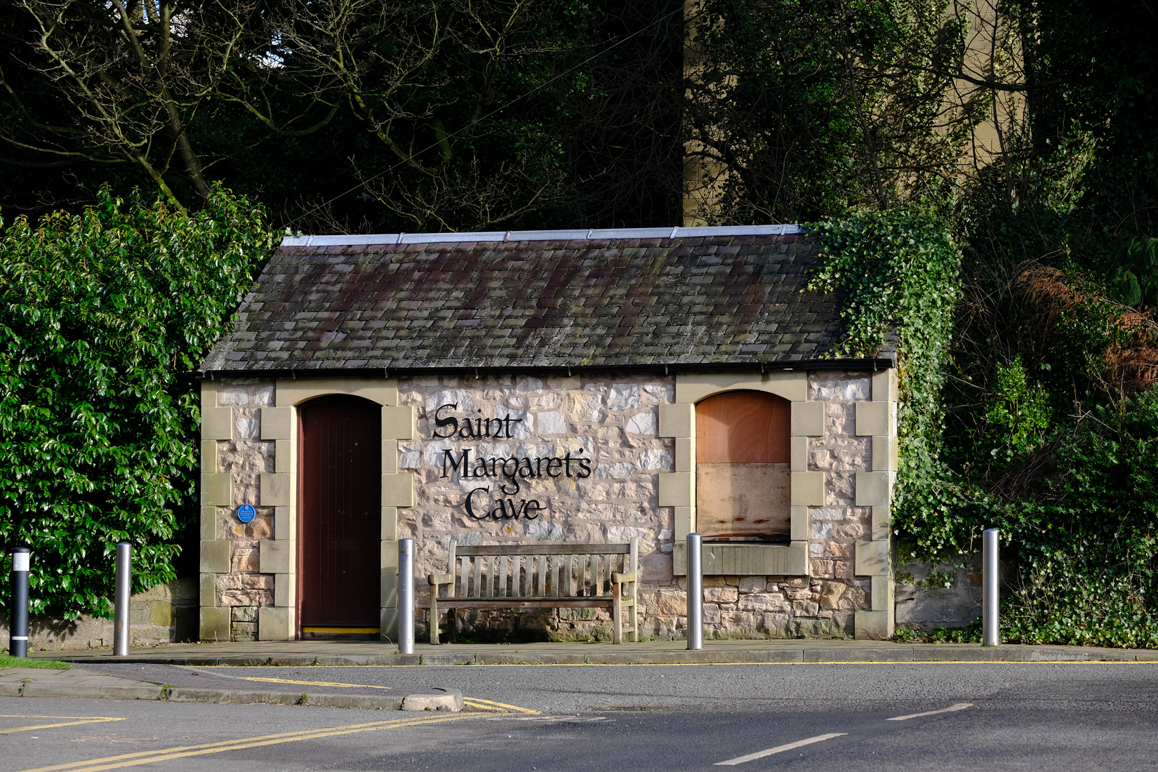 Small building surrounded by tress and road in front. It has writing Saint Margaret's Cave with doorway on left and window on right