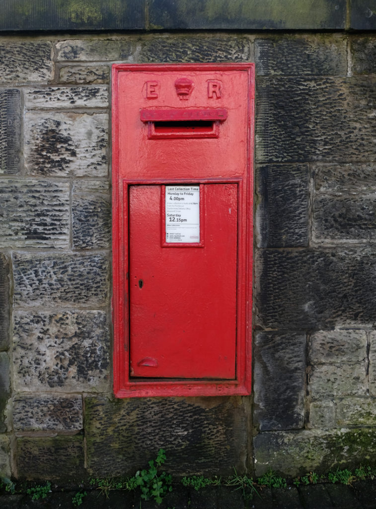 Red post box embedded into stone wall