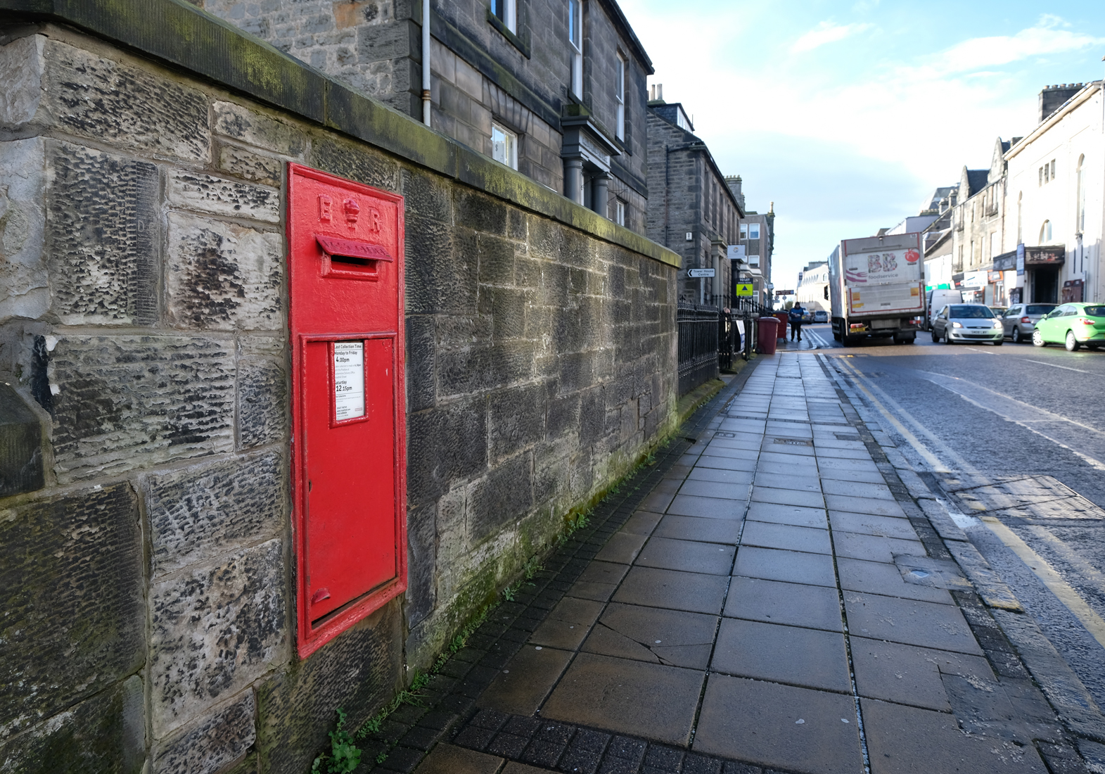 Red post box embedded in stone wall but pavement