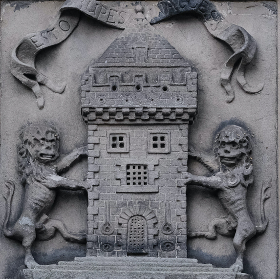 Carved stone. Tower of three stories in centre, flanked by lion each side on hind legs in rampant position.