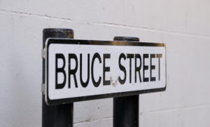 Street sign white background, black writing with Bruce Street.