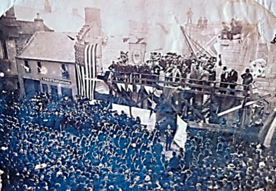 Black and white image from 1887 shows street filled with large crowd looking at a raised stage with bunting. On the stage is group of circa 50 people looking towards street crowd. Large American flag of 6metres hung on left of stage.