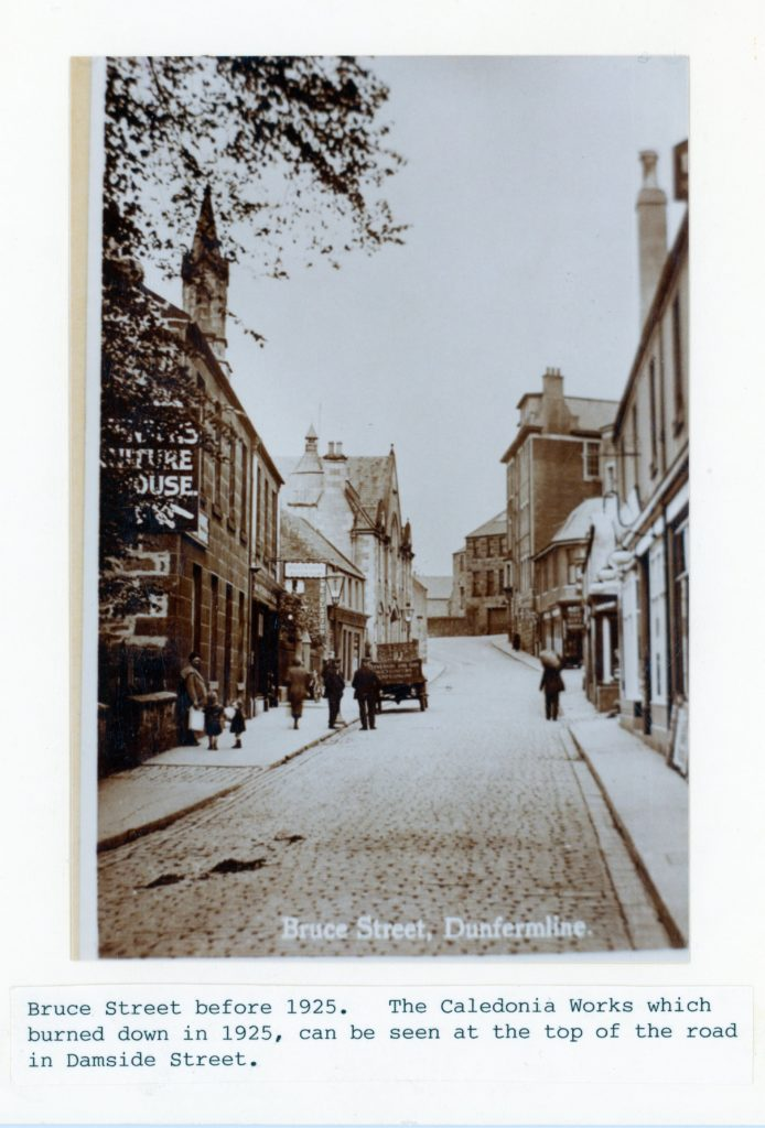 """Black and white photograph with description """"Bruce Street before 1925. The Caledonia Works which burned down in 1925, can be seen at the top of the road in Damside Street."""""""