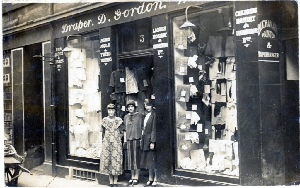 Black and white photo shop front of Draper. D. Gordon with three young ladies standing in doorway. Fashions look 1920s but unknown date for photo. Other writing on the shop uprights Childrens hosiery, ladies hosiery. Two windows, street to first floor filled with examples of shop stock.