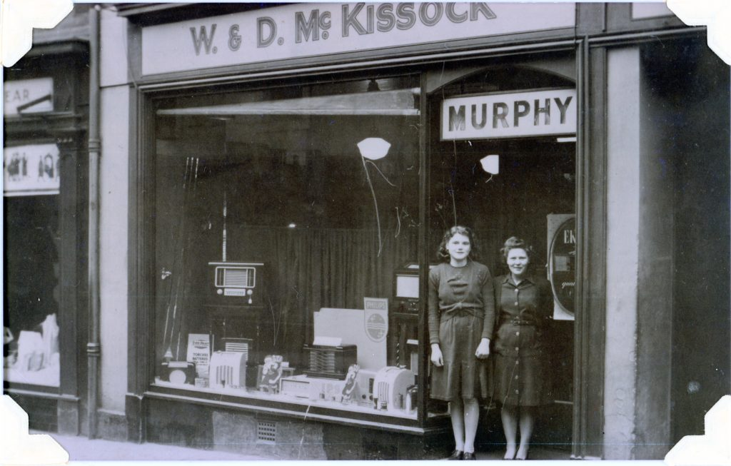 Black and white photo shop front of W & D McKissock with Murphy above the door. Two females standing in the doorway. one large pane window for shopfront and has electrical goods like television and wireless for sale. Dating picture with fashion and goods to be after 1960s.