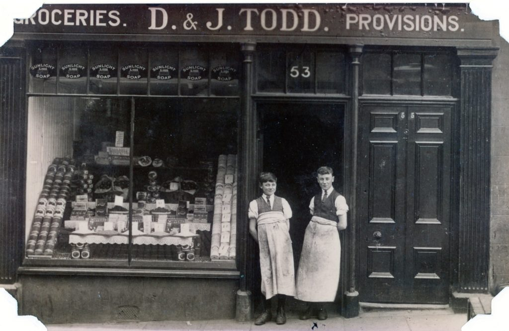Black and white photo shop front D & J Todd Groceries and Provisions. Shop number 53 above doorway with two young teenage boys (estimated age)  in the doorway. One large shop window with Sunlight Soap adverts at the top and canned produce in the window.