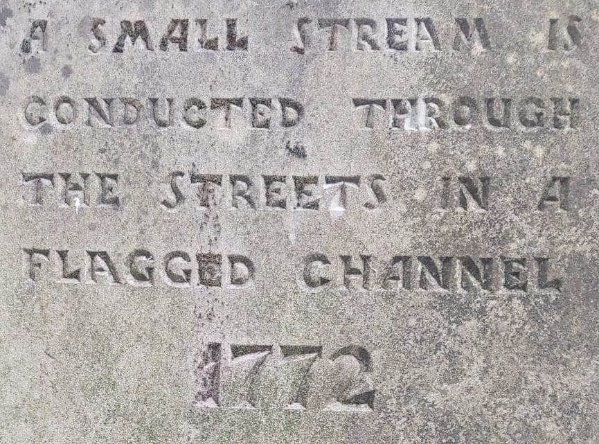Grey stone with carving saying, A small stream is conducted through the streets in a flagged channel, 1772
