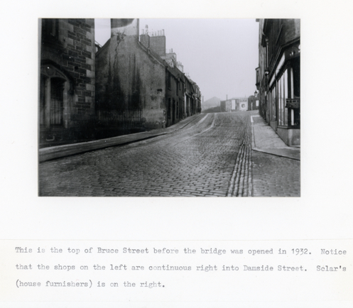 Black and white photograph with description 'This is the top of Bruce Street before the bridge was opened in 1932. Notice that the shops on the left are continuous right into Damside Street. Sclar's (house furnishers) is on the right.'