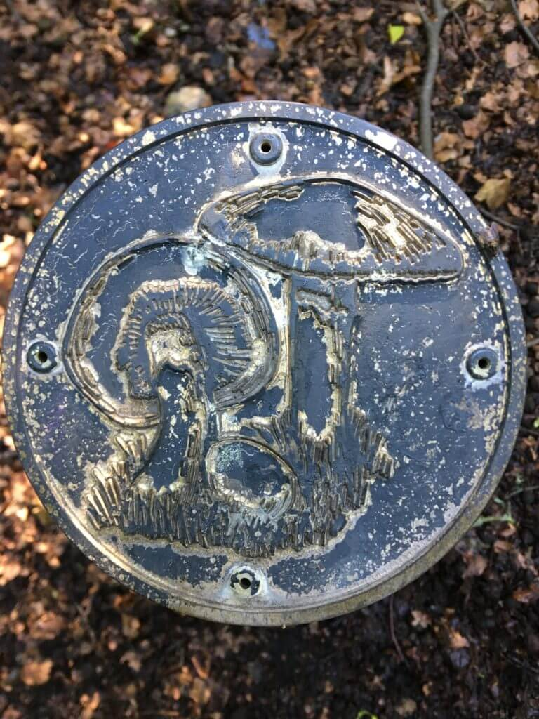 Circular plaque with image of two mushrooms in relief